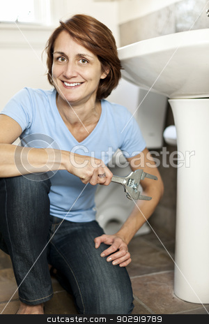 Woman fixing plumbing stock photo, Confident woman repairing sink in bathroom at home by Elena Elisseeva