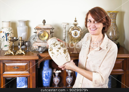 Woman with antique collection stock photo, Proud woman holding vase from her collection of antiques by Elena Elisseeva