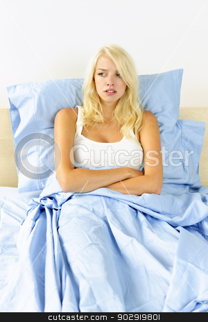 Woman upset in bed stock photo, Upset blonde woman sitting in bed with arms crossed by Elena Elisseeva