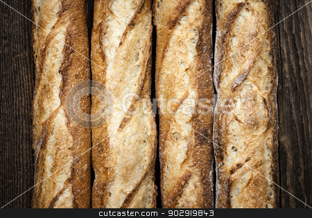 Baguettes stock photo, Baguette bread loaves in a row on wooden background by Elena Elisseeva