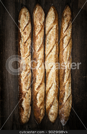 Baguettes stock photo, Four whole baguette bread loaves on dark wooden background by Elena Elisseeva