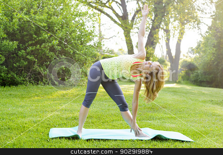 Woman in yoga triangle pose stock photo, Female fitness instructor doing yoga extended triangle pose outdoors in green park by Elena Elisseeva