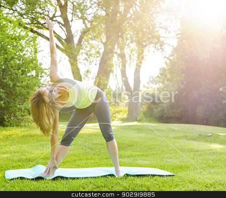 Woman in yoga triangle pose stock photo, Female fitness instructor doing yoga extended triangle pose outdoors in morning sunshine by Elena Elisseeva