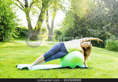 Woman on yoga balance ball stock photo, Female fitness instructor using yoga exercise ball in green park by Elena Elisseeva