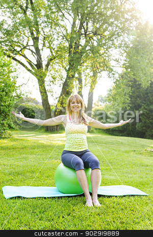 Woman on yoga balance ball stock photo, Female fitness instructor sitting on yoga exercise ball in green park by Elena Elisseeva