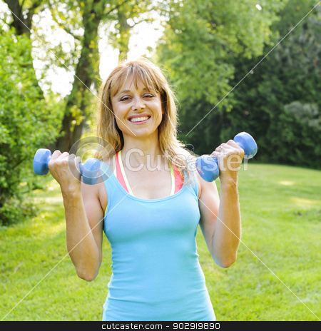 Woman exercising with dumbbells stock photo, Portrait of female fitness instructor exercising with small weights in green park by Elena Elisseeva