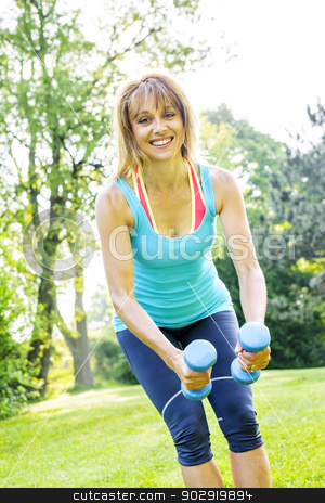 Woman exercising with dumbbells in park stock photo, Female fitness instructor exercising with small weights outdoors in green park by Elena Elisseeva