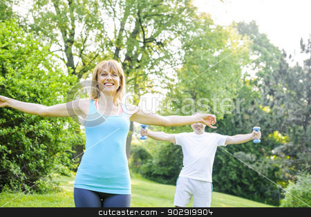 Personal trainer with client exercising outside stock photo, Female fitness instructor exercising with middle aged man outdoors in summer park by Elena Elisseeva