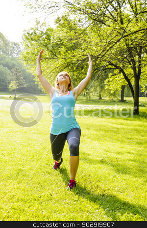 Woman exercising in park stock photo, Female yoga instructor in spiritual warrior pose at green park by Elena Elisseeva