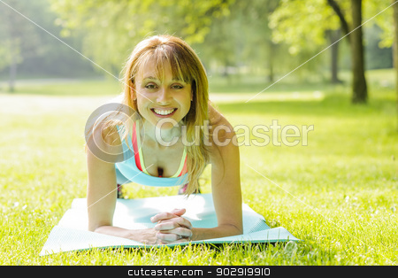 Woman holding plank pose outside stock photo, Female fitness instructor holding plank pose exercising outside in green summer park by Elena Elisseeva