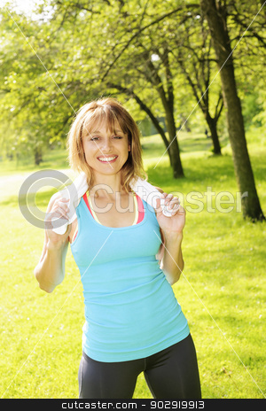 Woman exercising in park stock photo, Female fitness instructor standing with towel around neck after exercising in green park by Elena Elisseeva