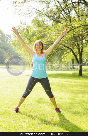 Smiling woman exercising outside stock photo, Female fitness instructor doing jumping jacks exercising in green park by Elena Elisseeva