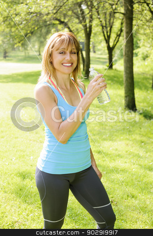 Active woman holding water bottle outside stock photo, Smiling female fitness instructor taking a break  with water bottle while exercising outdoor by Elena Elisseeva