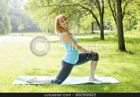 Smiling woman stretching in park stock photo, Happy female fitness instructor exercising in green spring park by Elena Elisseeva