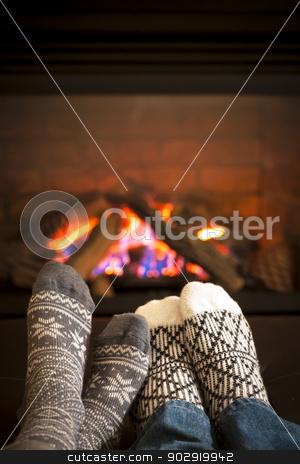 Feet warming by fireplace stock photo, Feet in wool socks warming by cozy fire by Elena Elisseeva
