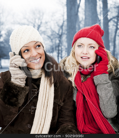Two girl friends on phones outside in winter stock photo, Portrait of two young female friends on the phone outdoors in winter by Elena Elisseeva