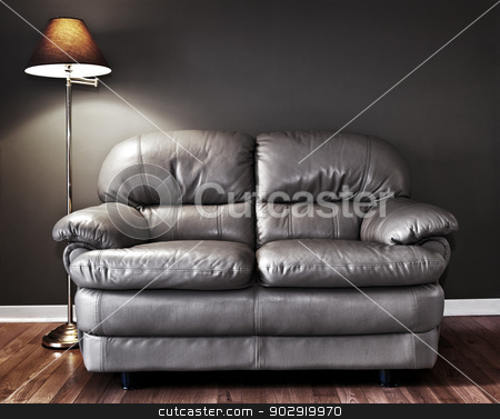 Couch and lamp stock photo, Leather love seat and floor lamp against dark wall by Elena Elisseeva
