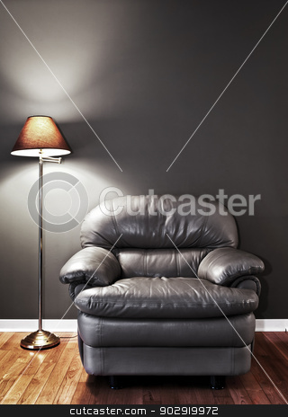 Armchair and floor lamp stock photo, Leather chair and floor lamp against dark wall by Elena Elisseeva