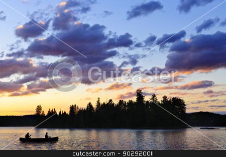Canoe on lake at sunset stock photo, Silhouette of island and canoe on lake at sunset in Algonquin Park, Canada by Elena Elisseeva