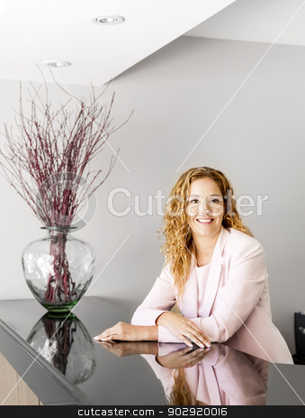 Smiling woman at office reception stock photo, Receptionist standing at reception counter in office by Elena Elisseeva
