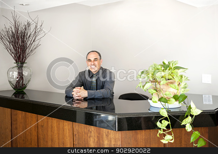 Smiling man standing at office reception stock photo, Businessman standing at reception counter in office by Elena Elisseeva