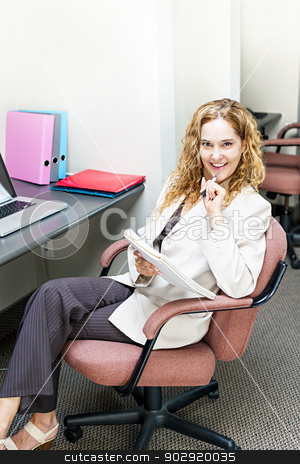 Business woman thinking at office desk stock photo, Smiling businesswoman thinking of ideas in office workstation by Elena Elisseeva