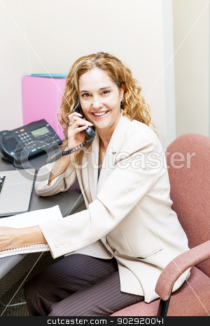 Smiling woman on telephone at office desk stock photo, Smiling businesswoman on phone in office workstation by Elena Elisseeva