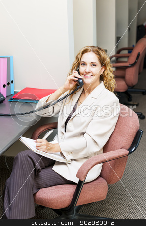 Smiling woman on telephone at office desk stock photo, Businesswoman on phone taking notes in office workstation by Elena Elisseeva