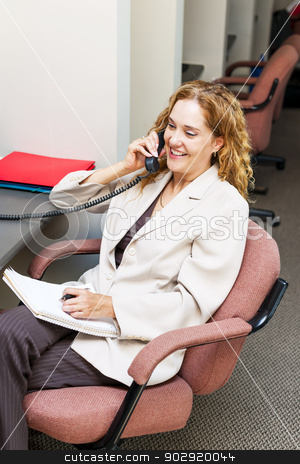 Smiling woman on telephone at office desk stock photo, Happy businesswoman on phone taking notes in office workstation by Elena Elisseeva