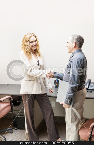 Man and woman shaking hands in office stock photo, Man and woman meeting in office shaking hands by Elena Elisseeva