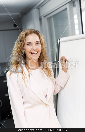 Business woman writing on flip chart stock photo, Smiling businesswoman writing on flip chart paper in office by Elena Elisseeva
