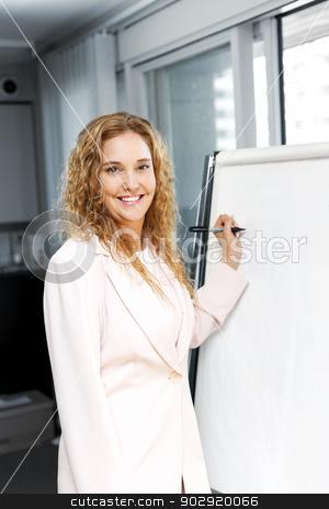 Business woman writing on flip chart stock photo, Smiling businesswoman writing on flip chart paper in office by Elena Elisseeva
