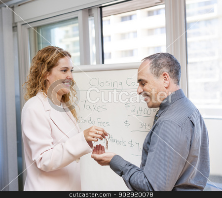 Real estate agent giving keys to client stock photo, Female real estate agent giving keys to new home buyer by Elena Elisseeva
