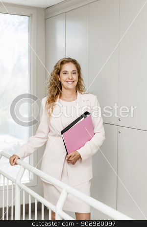 Successful businesswoman standing in hallway stock photo, Smiling powerful business woman standing in office hallway holding binder by Elena Elisseeva