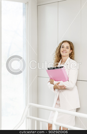 Smiling businesswoman standing in hallway stock photo, Happy confident business woman standing in office hallway holding binder by Elena Elisseeva