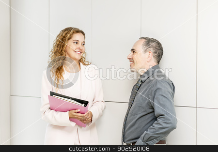 Business coworkers talking in hallway stock photo, Man and woman discussing work in business office hallway by Elena Elisseeva