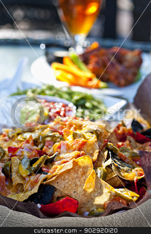 Nacho plate and appetizers stock photo, Basket of nachos and other appetizers on restaurant table by Elena Elisseeva