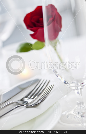 Romantic dinner setting in restaurant stock photo, Romantic restaurant table setting with rose candle plates and cutlery by Elena Elisseeva