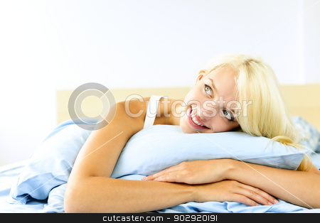 Pretty woman laying in bed daydreaming stock photo, Happy blonde young woman laying in bed dreaming and smiling by Elena Elisseeva