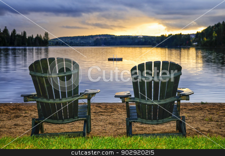 Wooden chairs at sunset on beach stock photo, Two wooden chairs on beach of relaxing lake at sunset. Algonquin provincial park, Canada. by Elena Elisseeva