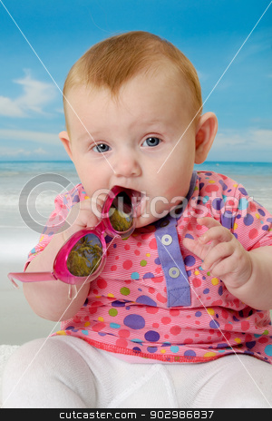 Baby on beach stock photo, Sweet baby on vacation on beach with the sea in the background. by Lars Christensen