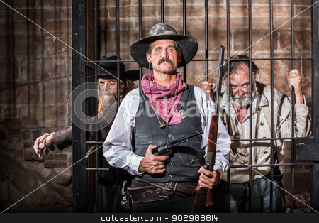 Sheriff Poses With Prisoner stock photo, Sheriff Stands Stern in Front of a Jail Cell by Scott Griessel