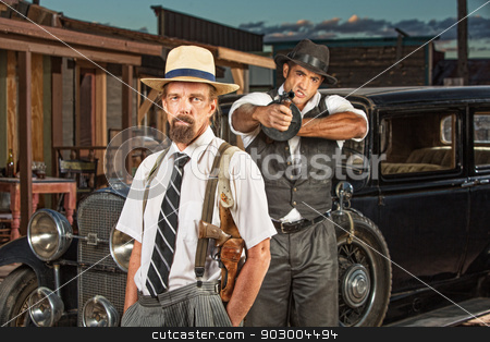 Calm Mobster with Guard stock photo, Calm vintage mobster with pistol and guard aiming machine gun by Scott Griessel