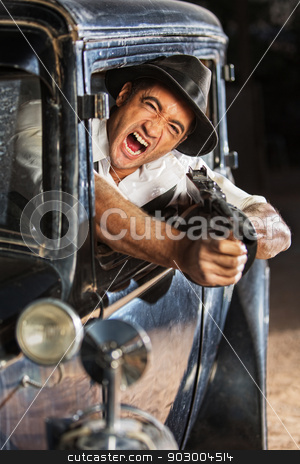 1920s Era Drive By Shooting stock photo, Yelling man firing submachine gun from vintage 1920s car by Scott Griessel