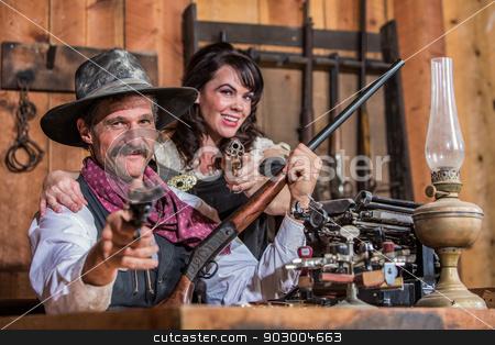 Smiling Sheriff Points Gun With Woman stock photo, Smiling Sheriff Stands With Woman and a Loaded Gun by Scott Griessel