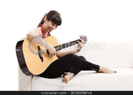 Playing guitar stock photo, Beautiful woman sitting on the sofa and playing guitar, isolated on white by ikostudio