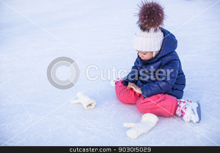Little adorable girl sitting on ice with skates after the fall stock photo, Little adorable girl sitting on the ice with skates after the fall by Dmitry Travnikov