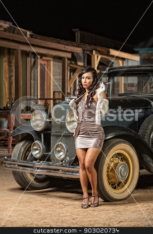 Pretty Lady Smoking Near Old Car stock photo, 1920s era woman with cigarette next to antique car by Scott Griessel