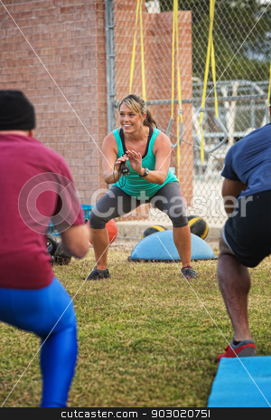 Cheerful Fitness Instructor stock photo, Cheerful boot camp fitness instructor squatting by Scott Griessel