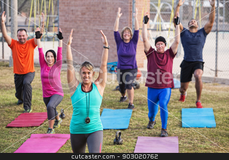 Active Adults Exercising stock photo, Group of active adults stretching outdoors with mats by Scott Griessel